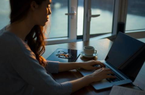 Chica escribiendo en computadora con libreta, taza y anteojos sobre la mesa