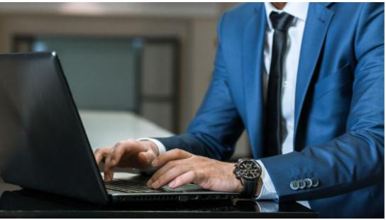 Hombre formal escribiendo en computadora.